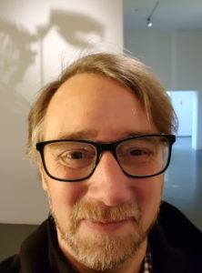Selfie in museum met de schaduw van een skelet achter me.